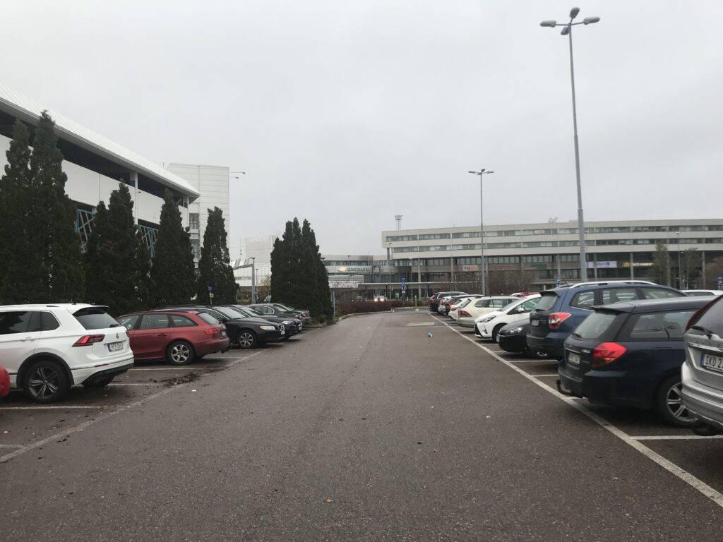 Ödslig parkeringsplats under en grå himmel. Bilar, men inte en enda människa.