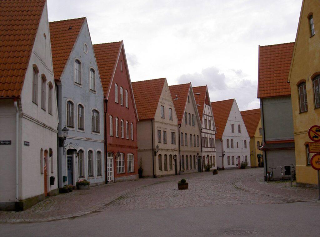 Gata lagd med gatsten. På ömse sidor hus som ser medeltida ut. Putsade fasader, ett i korsvirke. Folktomt. Svensk trafikskylt motorfordonstrafik förbjuden höger i bild, kompletterad med kinesisk motsvarighet.
