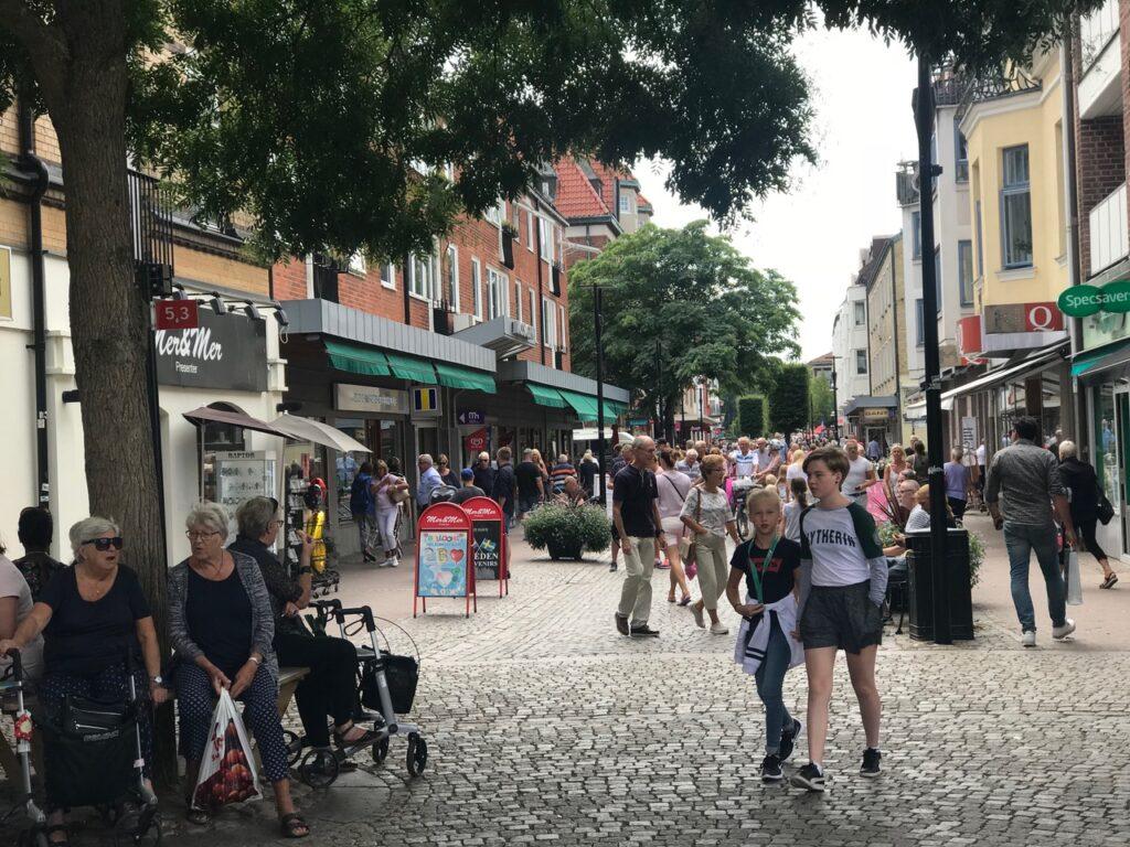 Livfull gågata en sommardag. Människor i alla åldrar promenerar. Kvinnor med rollatorer vilar.