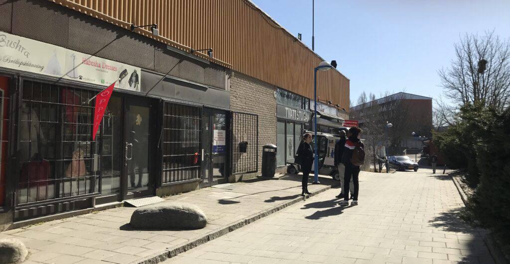 Vårvinterljus. Mitt på dagen. Butik öppen MEN galler för skyltfönstren och stora stenar på trottoaren. Buskage till höger i bilden.