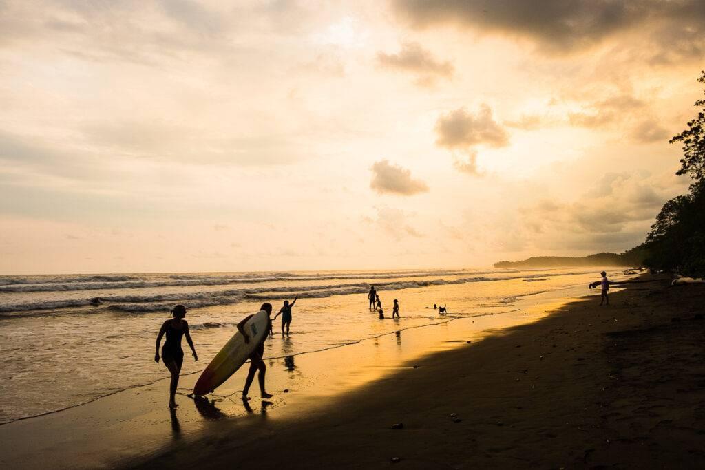 Badare och surfare på väg upp ur vattnet i solnedgången i Uvita.