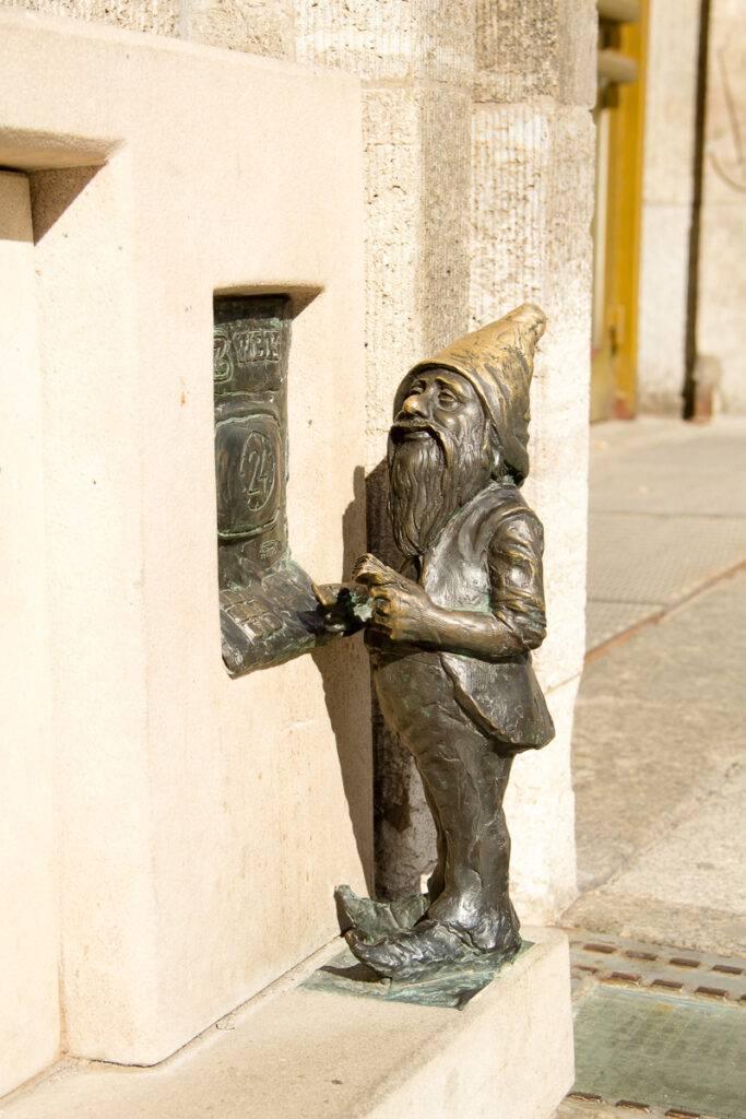 En bronsdvärg tar ut pengar i en minibankomat. Foto: ELISABET AXÅS