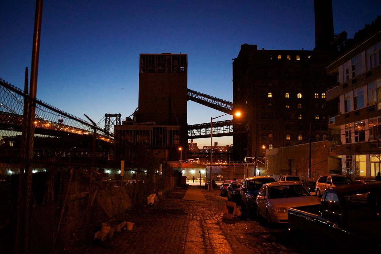 Mörk bild, ödslig plats, höga byggnader med slutna fasader