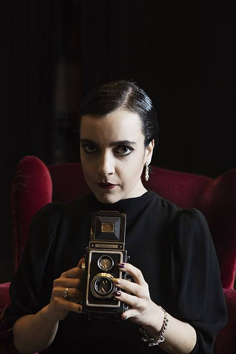 Shima Niavarani, sminkad, klädd i elegant svart klänning med gammeldags kamera i hand