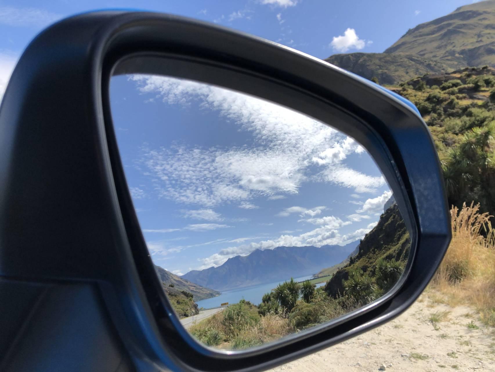 Nya Zeeländskt landskap i bilens sidospegel