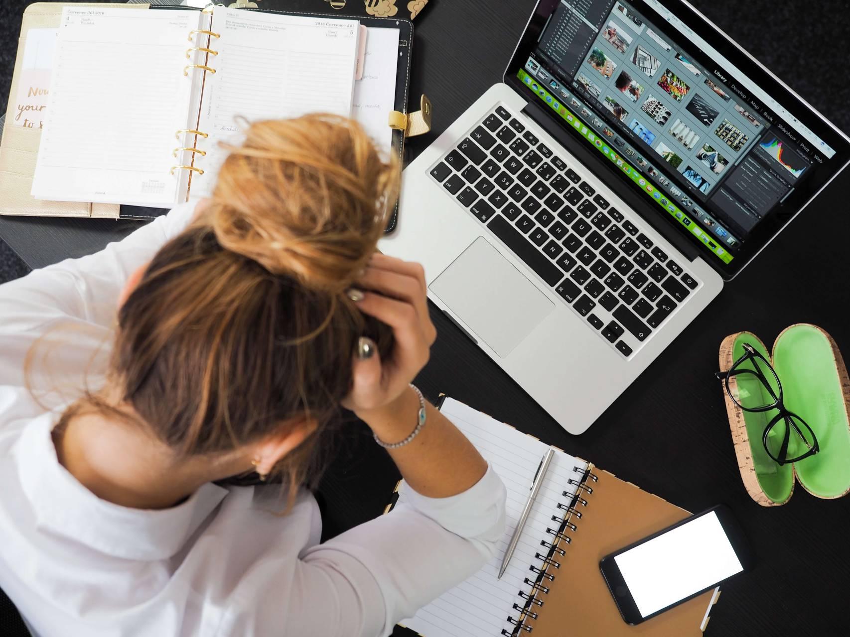 Kvinna framför laptop med huvudet i händerna