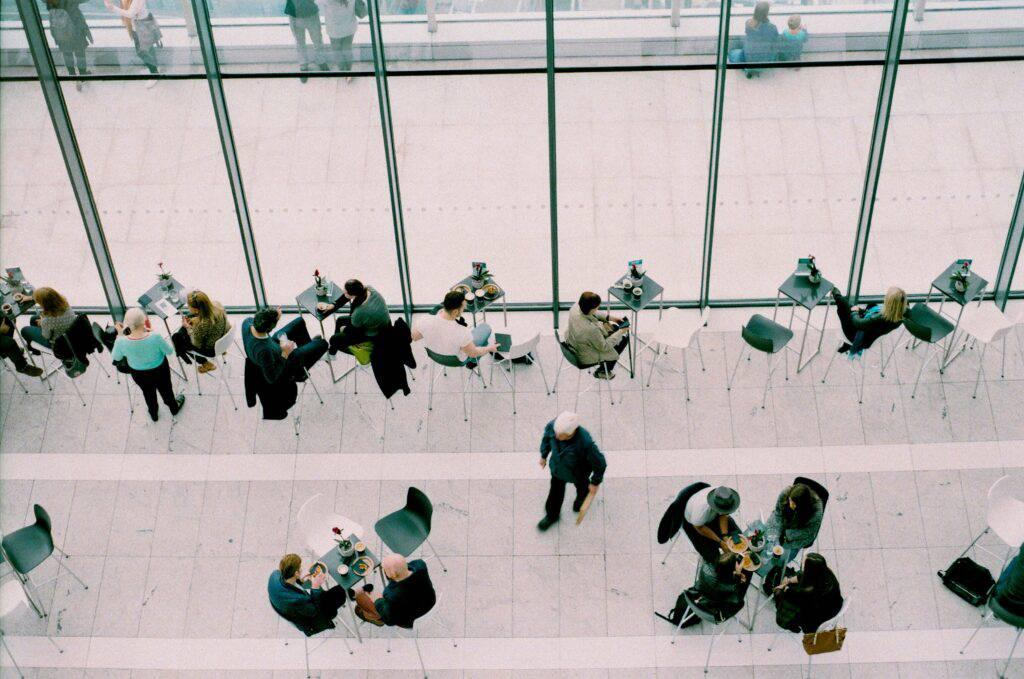 Cafemiljö med glasväggar där människor sitter runt små bord