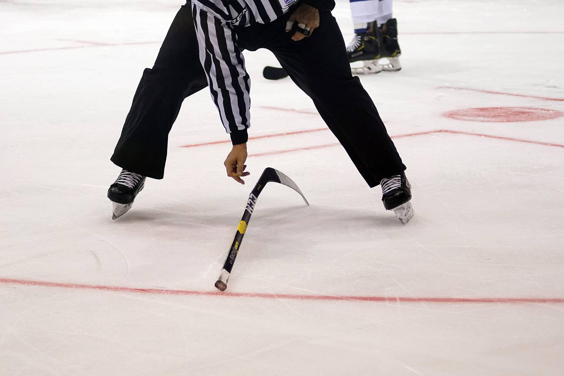 Hockeymålvakt plockar upp trasig klubba