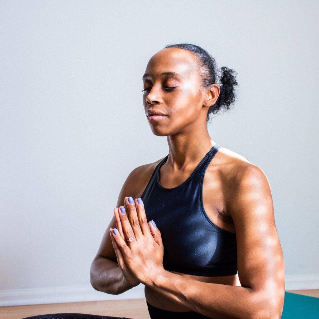 Kvinna mediterar i solljus