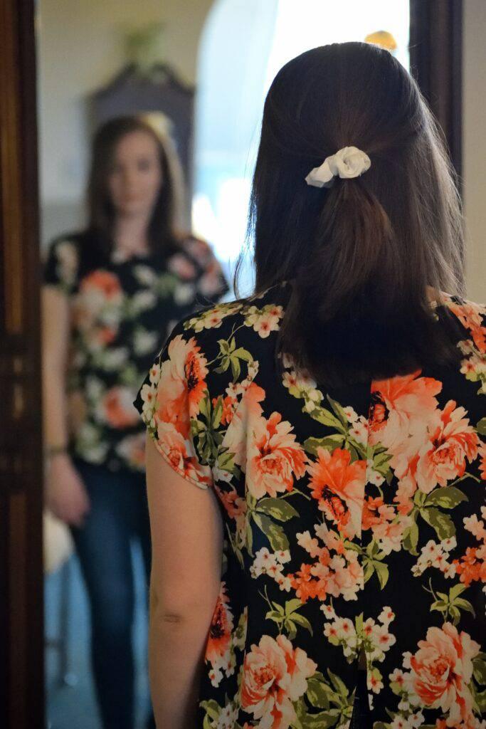 Kvinna bakifrån i blommig klänning framför spegel