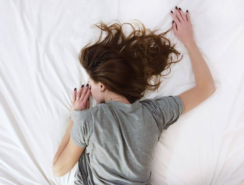 Kvinna ligger på mage i en säng