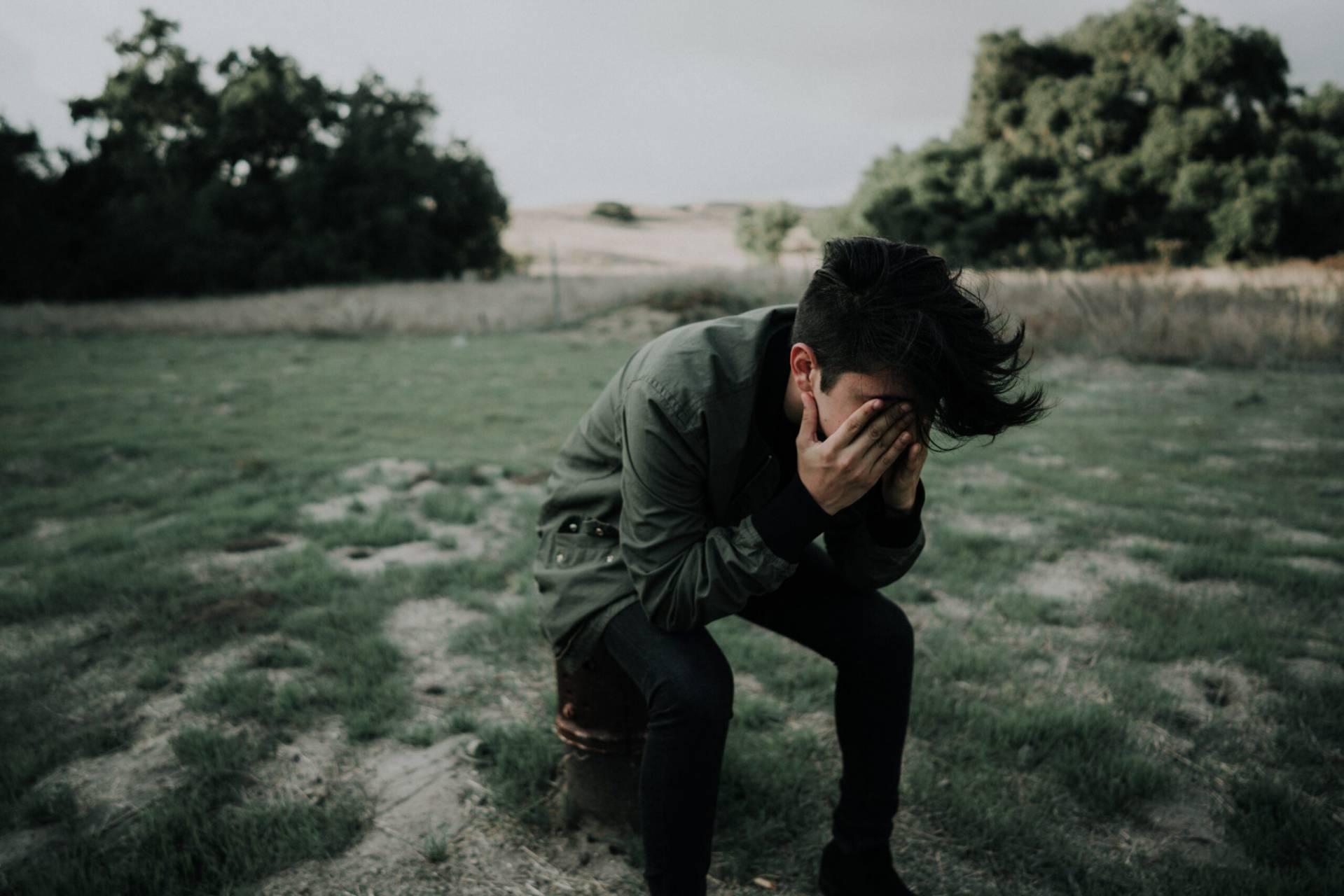 Ung man sitter med ansiktet begravt i händerna