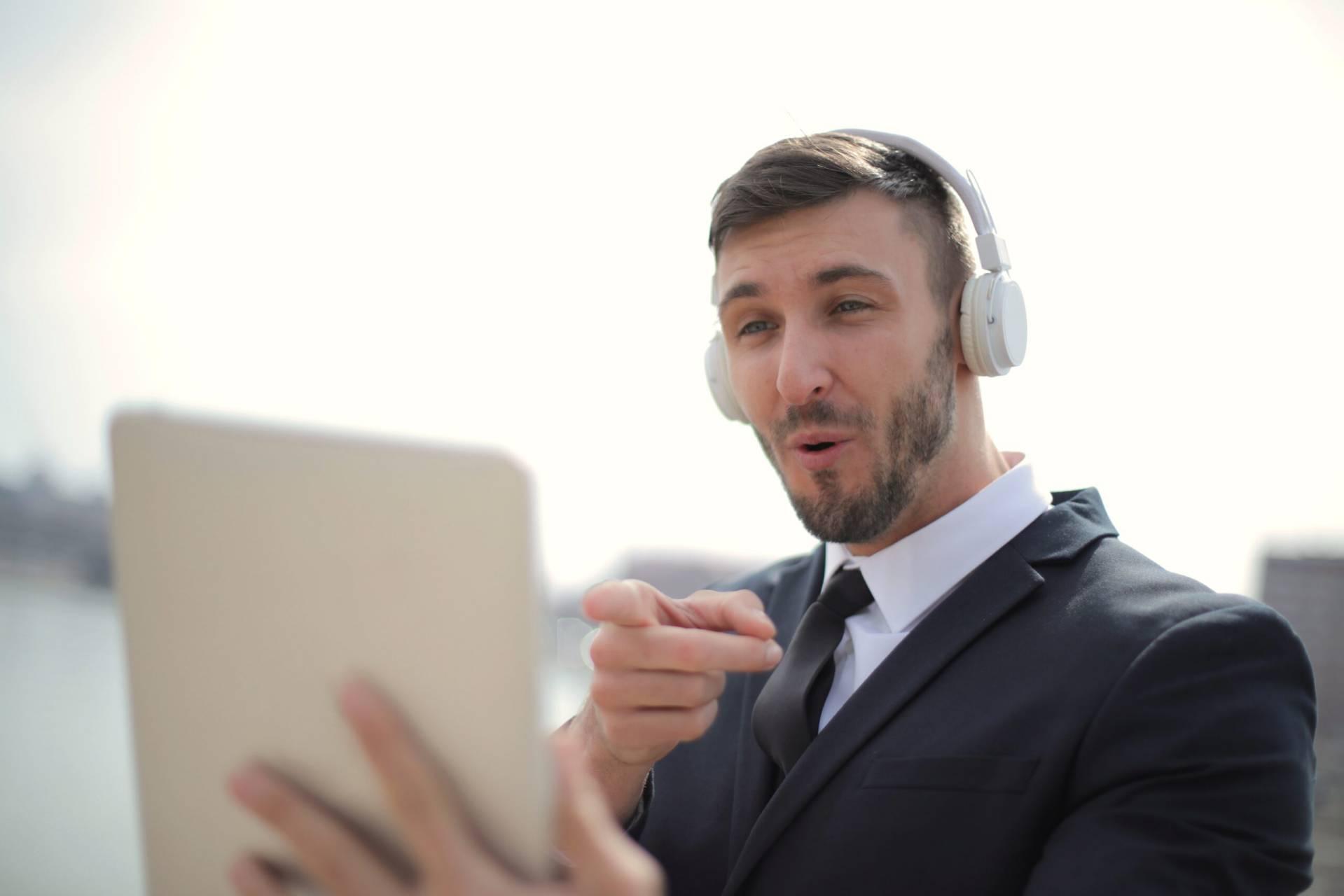 man i svart kostym med iPad och hörlurar