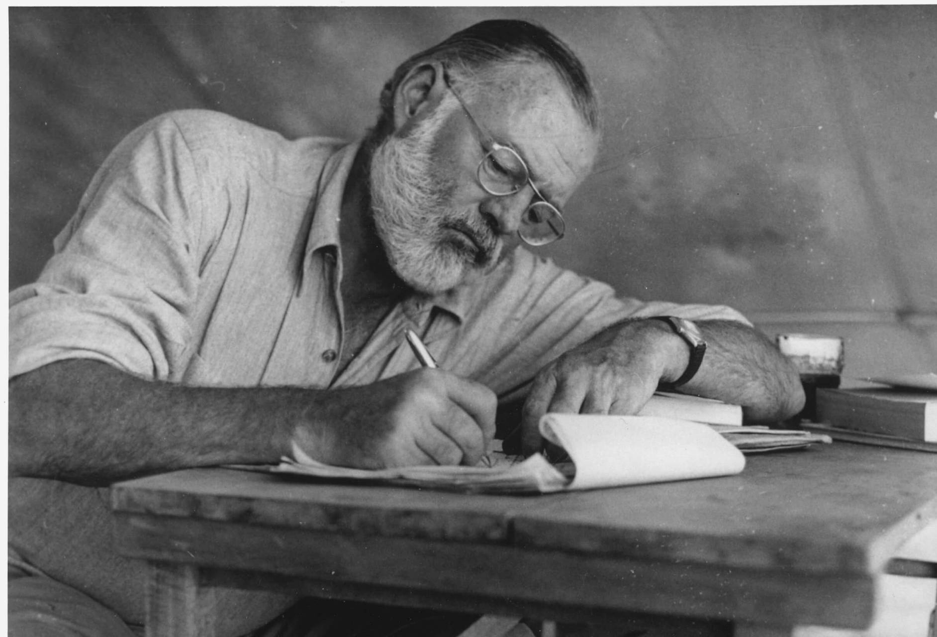 Hemingway lutad över ett anteckningsblock