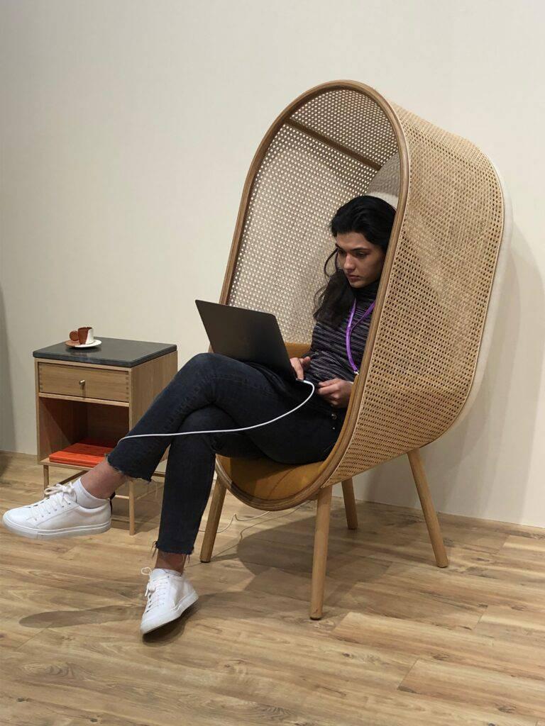 EN kvinna sitter bekvämt hemma i mysfåtölj med laptop i knät. Hon är koncentrerad på sitt arbete.