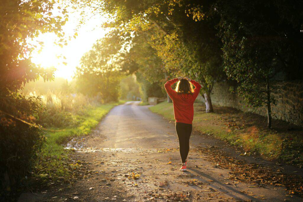 Kvinna på skogsväg i motljus