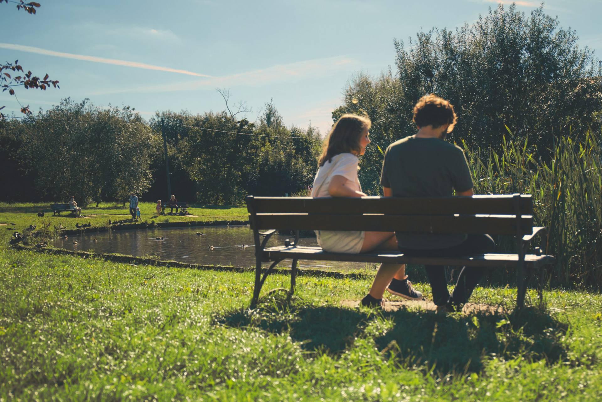 Man och kvinna sitter i solljus på en bänk omgiven av grönska