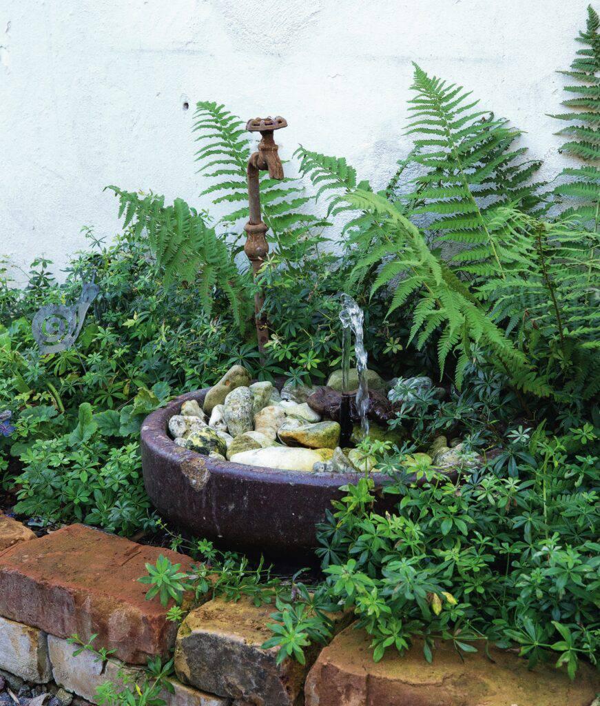 Porlande vatten i ett hörn av trädgården.