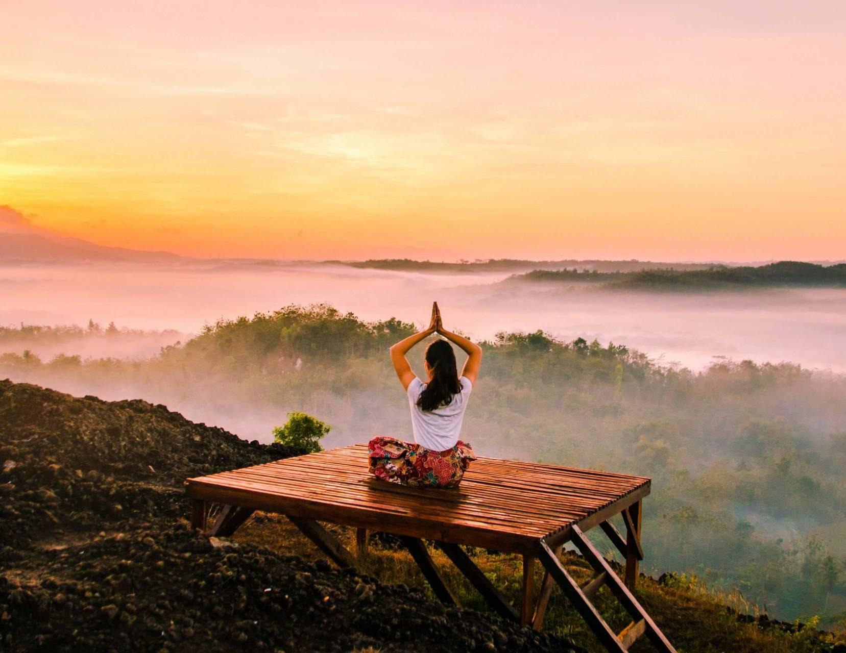 Kvinna i meditationsställning, solnedgång i djungeln