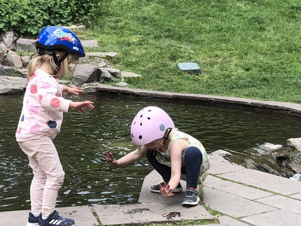Två små flickor vid en damm