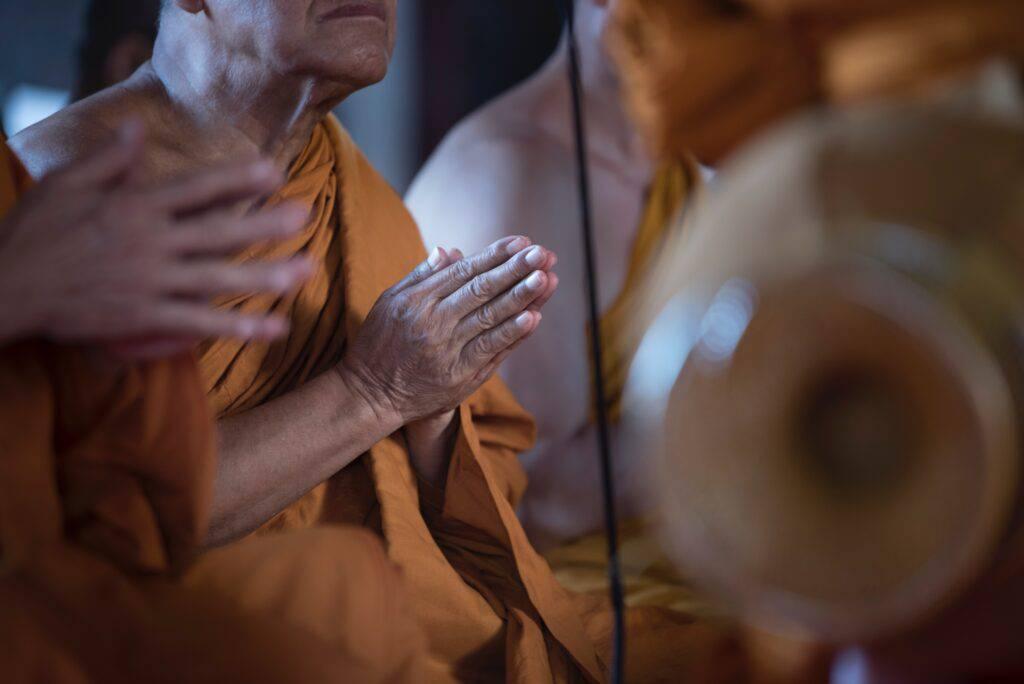 Buddhistmunk som ber, händer framför hjärtat