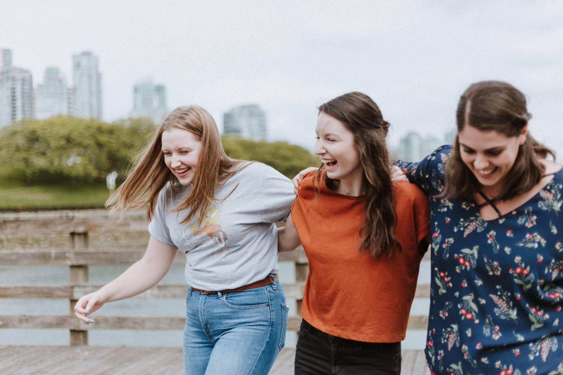 Tre unga glada kvinnor med armarna om varandras axlar.