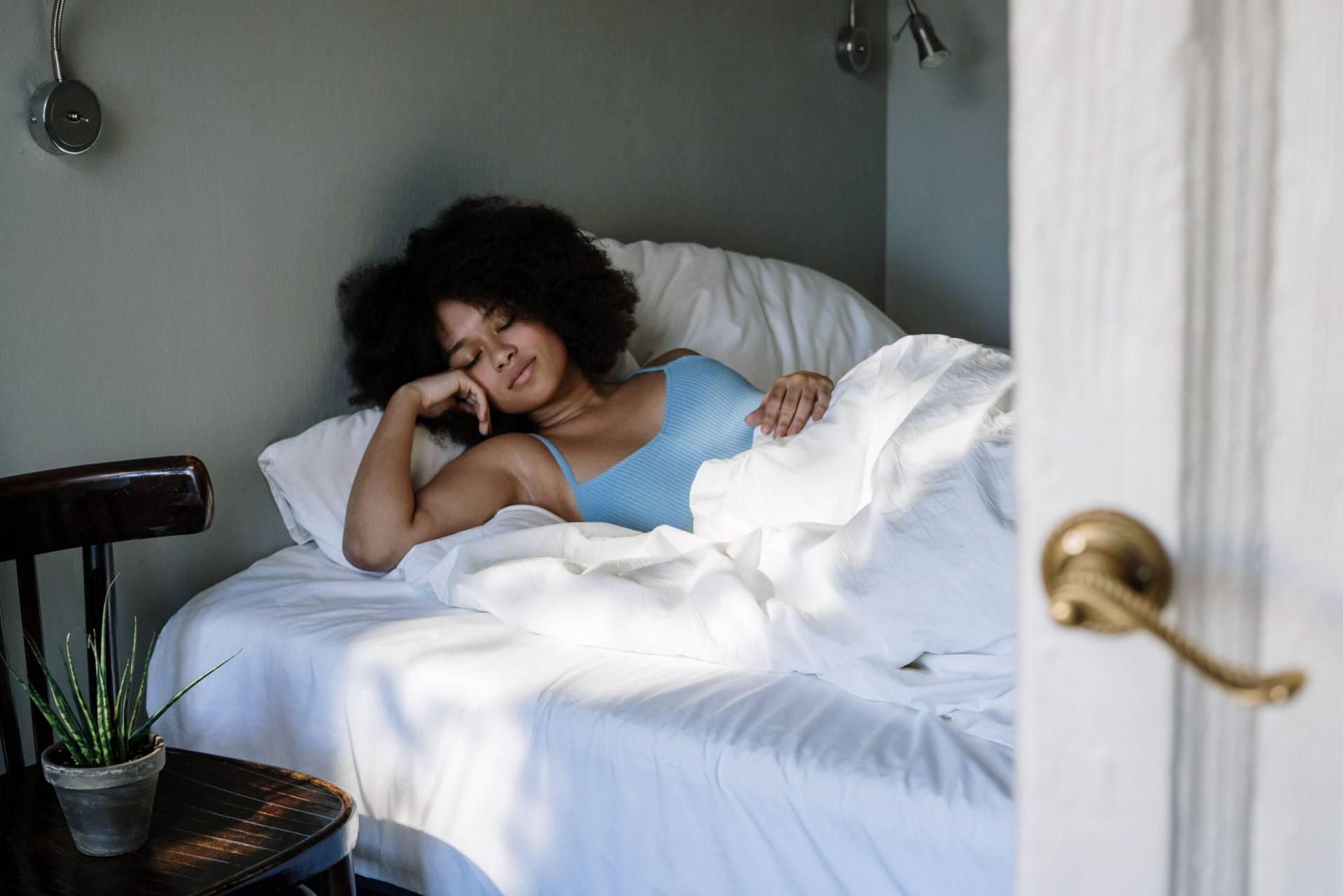 Kvinna sover på vita lakan