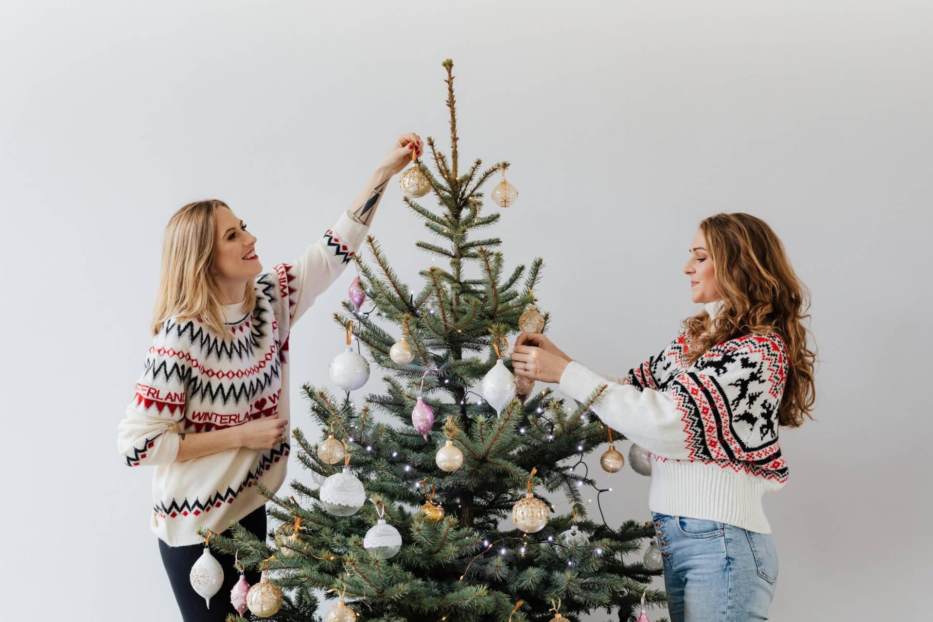 Två kvinnor jultröjor klär en julgran