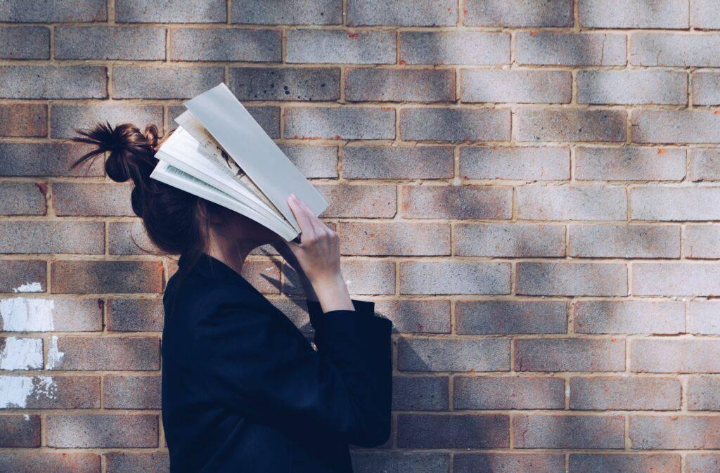 Tjej som täcker ansiktet med en öppen bok