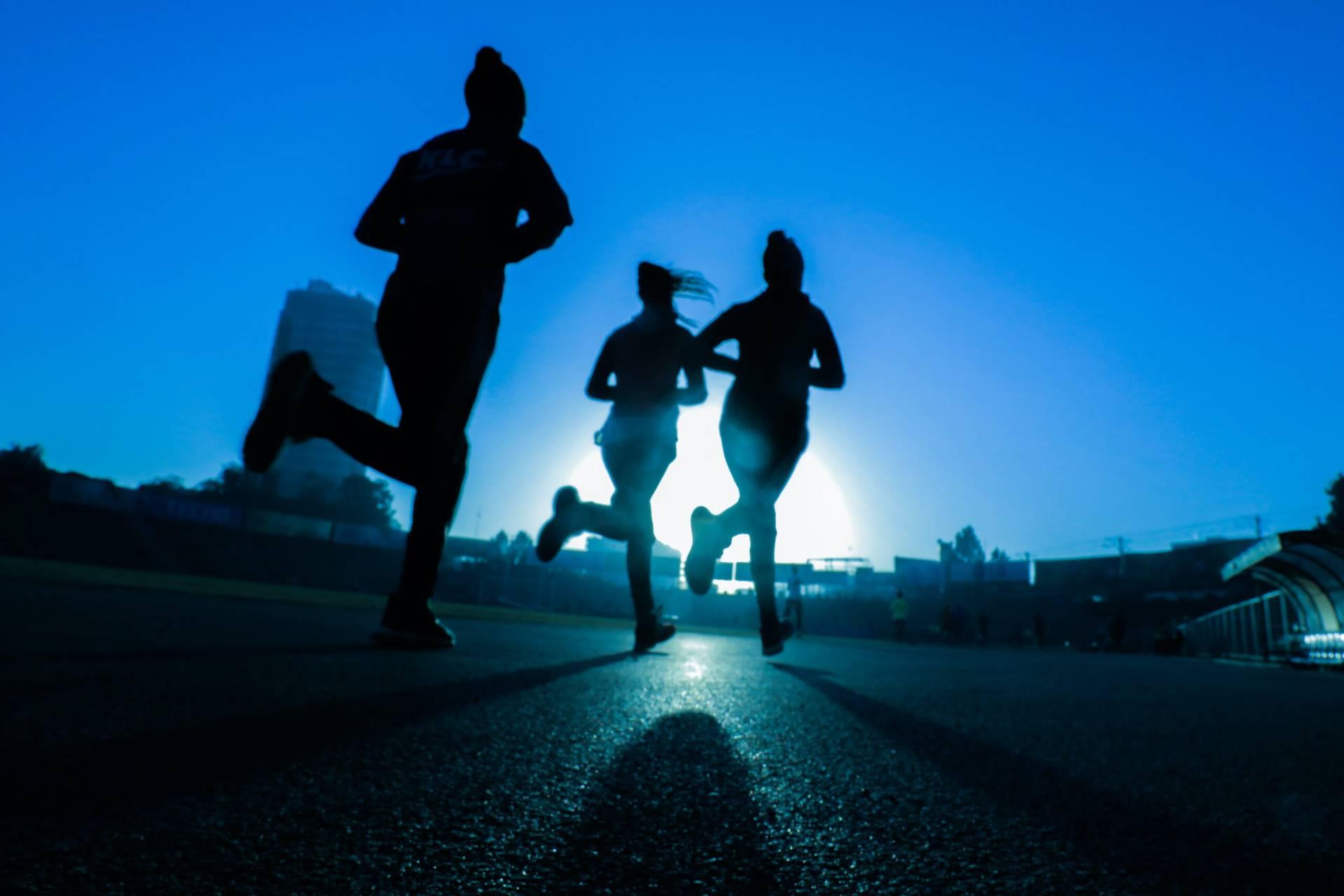 Löpare som springer på upplyst väg