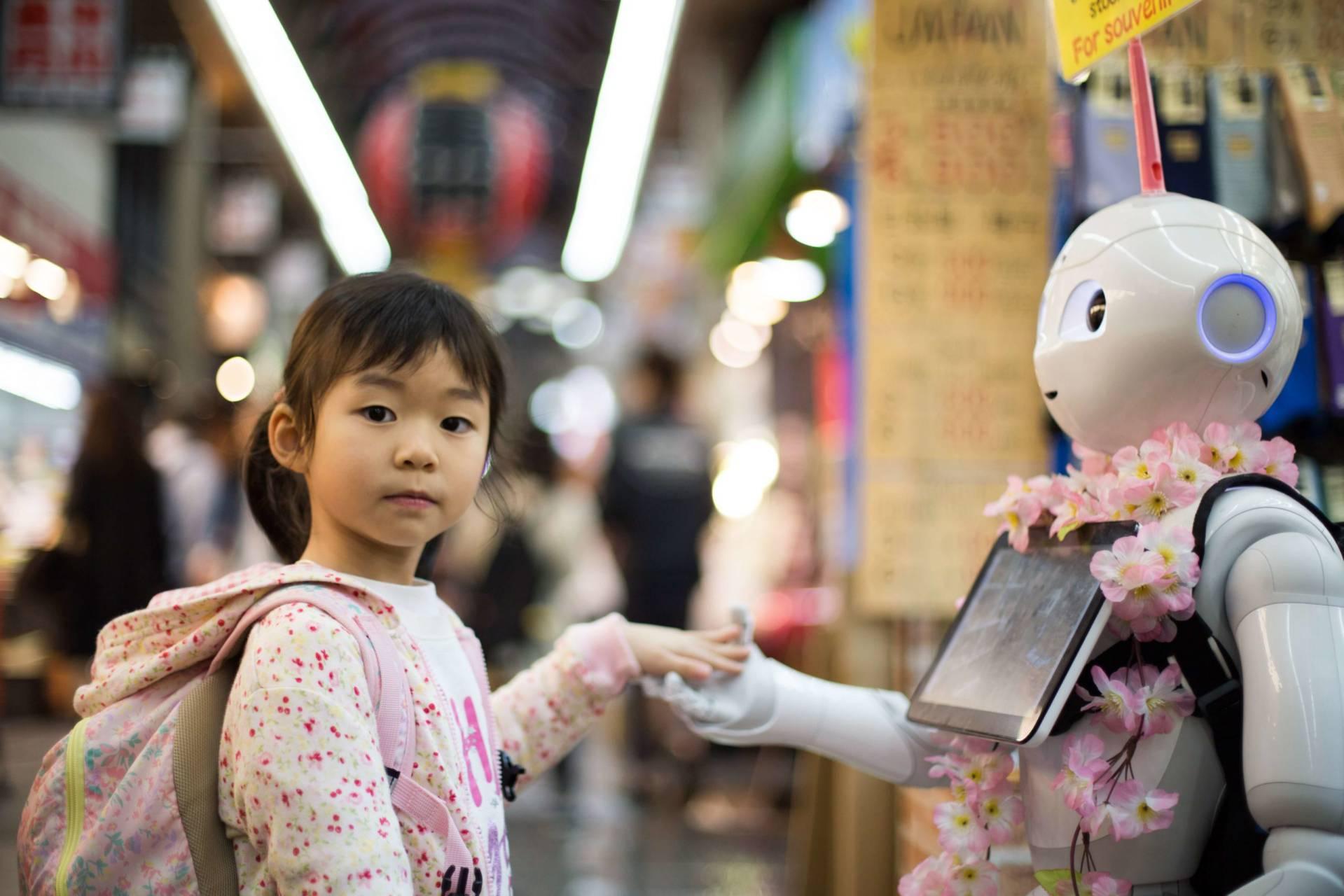 Flicka håller en robot i hand