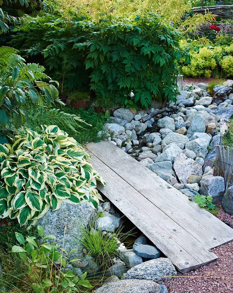 Invid frodiga perenner passerar bäcken, över går träbroar av enkla plankor.